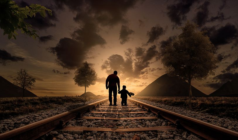 Father and Son on a lonely railway at sunset