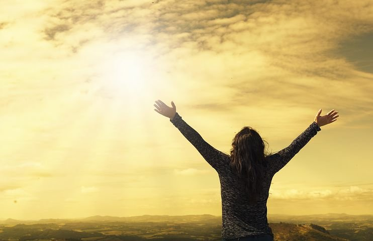 A woman with an outstretched arm looking up to Heaven with bright evening light